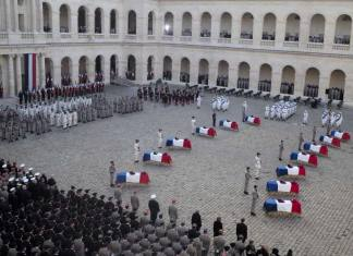 Coffins of 13 French soldiers killed in Mali lay at the Invalides monument during a ceremony Monday Dec.2, 2019 in Paris. In its biggest military funeral in decades